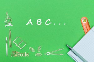 letters abc, school supplies wooden miniatures, notebook with ruler, pen on green backboard
