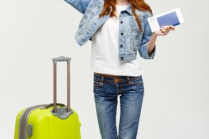 Travel Concept: Full-length young happy surprised beautiful woman holding green suitcase over white background