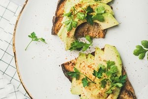 Flat-lay of avocado toast on plate over grey marble background