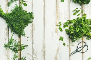 Various fresh green kitchen herbs over wooden background, copy space