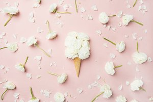 Waffle cone with white buttercup flowers over light pink background