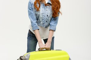 Travel and Lifestyle Concept: Young woman suffers from back pain lifting a heavy suitcase isolated on white background