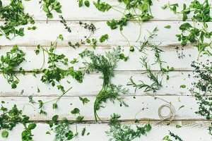 Various fresh green kitchen herbs for healthy cooking, wide composition