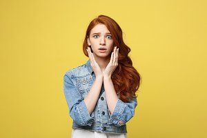 Close up Portrait young beautiful attractive redhair girl worry with something. Golden yellow Background. Copy space.