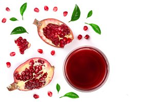 A glass of pomegranate juice with fresh pomegranate fruits decorated with leaves isolated on white background. Top view