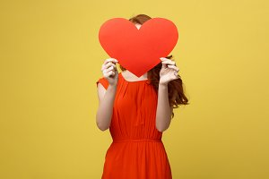 Joyful caucasian girl in orange gorgeous dress holding red heart cover her face. Shallow depth of field. Valentine day concept.