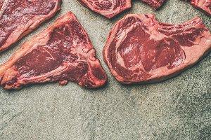 Porterhouse, t-bone and rib-eye steaks over grey background, square crop