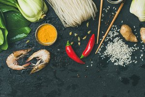 Asian cuisine ingredients over dark slate stone background, square crop