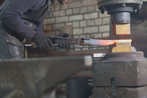 Man blacksmith forges the metal at the mechanical hammer