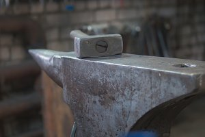 Inside forge workshop - steel vise, hammer and hot furnace