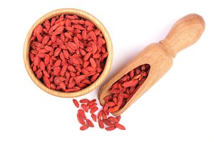 Dried goji berries in wooden bowl and scoop Isolated on white background