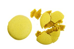 broken yellow macarons isolated on white background closeup