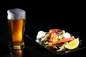 Glass of cold light beer and salad w