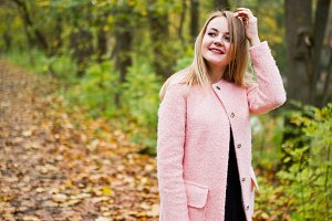 girl at pink coat posed on autumn