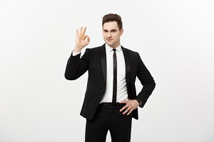 Business Concept: A handsome man in smart suit isolated on gray background showing ok sign.