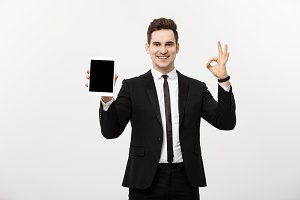 Business Concept: Cheerful businessman in smart suit with pc tablet showing ok. Isolated over grey background.