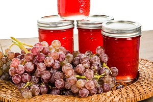 Jars of grape jelly with grapes