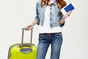 Full length of young beautiful female in denim walking with the travel bag and passport, isolated on white background