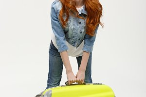 Travel and Lifestyle Concept: Young happy beautiful woman holding green suitcase over white background