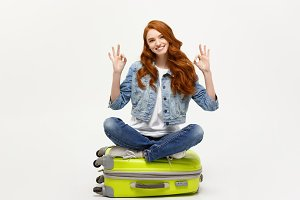 Travel and Lifestyle Concept: Young caucasian Woman sitting on suitcase and showing ok finger sign. Isolated on white.