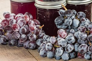 Purple grapes with jars of jelly