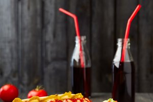 Two hot dogs with drinks on wooden background