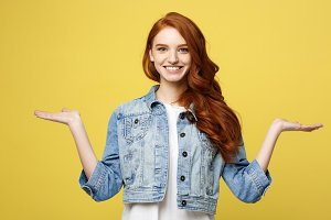 Lifestyle Concept: Surprised young woman with hand on side over golden yellow background. Looking at camera.