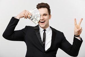 Portrait of a successful confident man showing bunch of money banknotes and showing victory finger sign isolated over white background