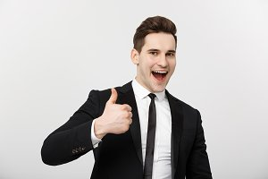 Business Concept: Portrait of excited man with opened mouth dressed in formal wear giving thumbs-up against gray background