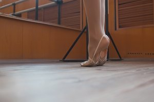 Ballet dancer's feet in scenic shoes training in studio