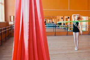 Rhythmic gymnastics - young woman training a gymnastics exercise with a green ribbon