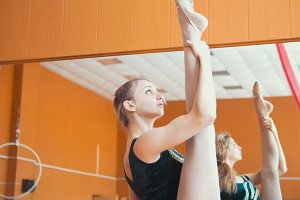 Young athletic woman gymnast doing stretching leg on barre in a studio