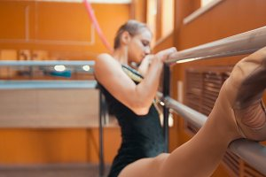 Young woman gymnast doing stretching leg on barre in a studio