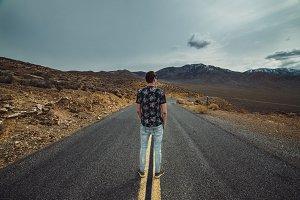 Man standing on empty desert road