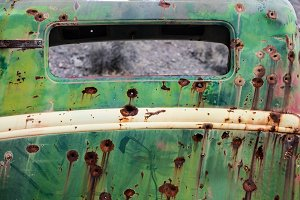 Rusty old car metal with bullet hole