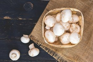 White champignons in a wooden basket.
