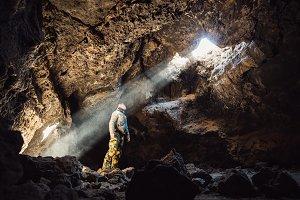 Man standing under cave light