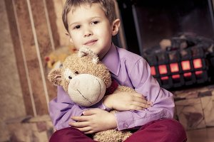 Boy, soft toy and fireplace