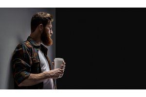 Bearded man drinking cappuccino coffee to go