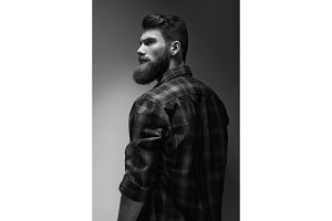 Single standing in profile young handsome serious bearded man