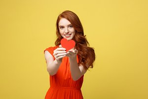 Portrait of happy romantic young caucasian girl with red paper heart-shaped postcard, romantic wishes, Valentine day celebration, love concept
