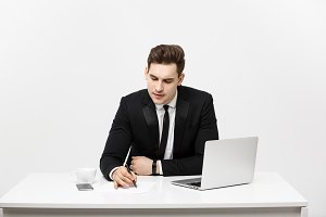 Concentrated young businessman writing documents at office desk.