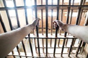 Prisoner man in jail holding hands