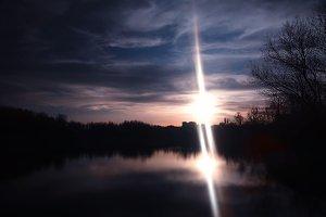 Dramatic sunset on park lake bokeh background