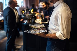 Waiter carrying drinks on event