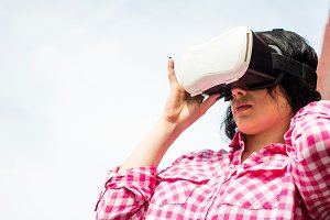A young woman is wearing VR glasses.