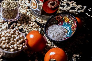 raw healthy fresh food cereals seeds and grain with tomatoes and bottle dish