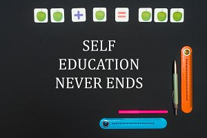 Black art table with stationery supplies with text self education never ends on blackboard