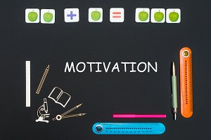Above stationery supplies and text motivation on blackboard