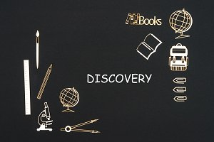 School supplies placed on black background with text discovery